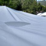 Lavor vody na sluneční plachtě po celonočním dešti